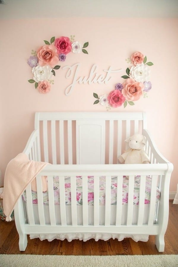 Image of crib with paper flower wall decor