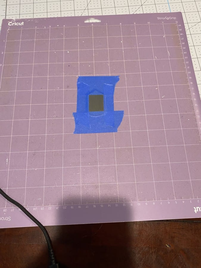 Dog tag centered on Cricut mat with tape